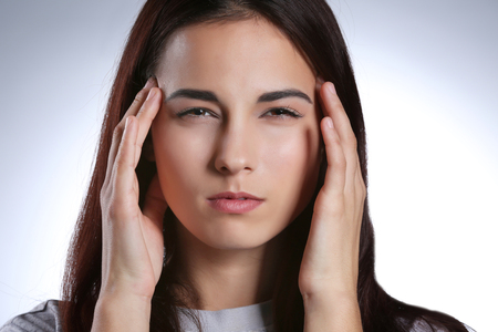 Young woman suffering from headache on light background, closeup