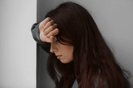 Depressed young woman standing near wall at home, closeup Stock Photo