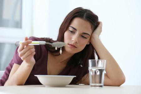 Deprimierte Frau, die am Küchentisch ohne Appetit sitzt