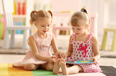 Cheerful little girls with book sitting on the floor