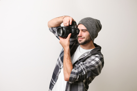 Handsome young photographer on light background