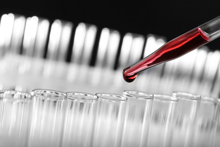 Closeup of a pipette dropping a red sample into a test tube on blurred background