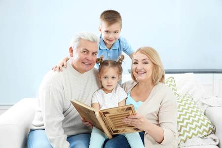 Grandparents looking at photo album with their grandchildren 스톡 콘텐츠 - 109858052
