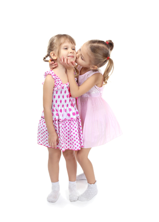 Adorable little sisters in beautiful dresses kissing on white background 版權商用圖片