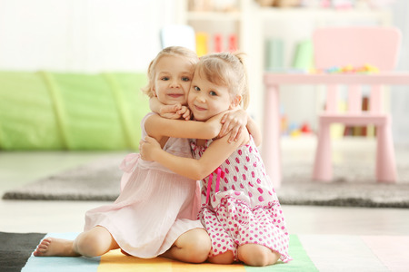 Adorable little girls in beautiful dresses embracing in the room