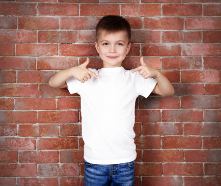 Cute boy in white T-shirt on brick wall background
