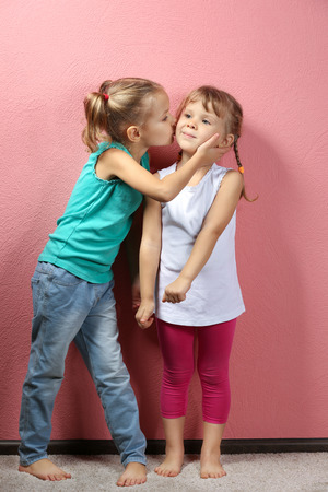 Adorable little girls on pink background