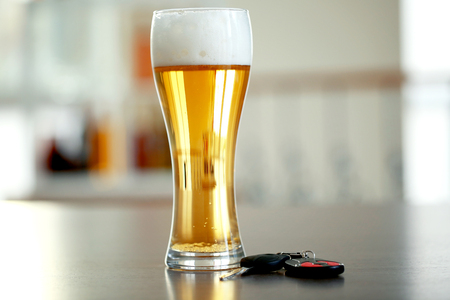 Glass of beer and car key on table. Don't drink and drive concept Imagens