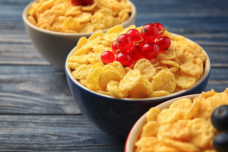 Bowls with cornflakes and berries on grey wooden background, closeup