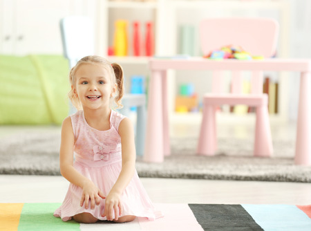 Cute little girl sitting on the floor at home Foto de archivo