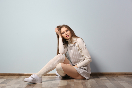 Beautiful young woman sitting on floor near light wall 免版税图像