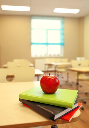 Stack of books and apple on desk at classroom Banque d'images - 108222641