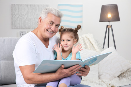 Grandfather reading his granddaughter book