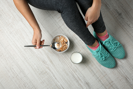 Woman sitting on the floor with healthy breakfast