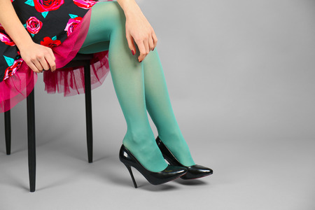 Woman wearing stockings and high heels on color background
