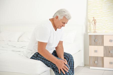 Senior man die lijdt aan pijn in de slaapkamer