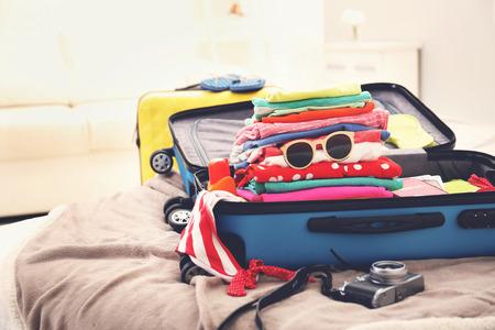 Opened traveler case on bed Foto de archivo