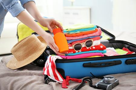 Manos femeninas embalaje maleta de viajero en la cama, primer plano