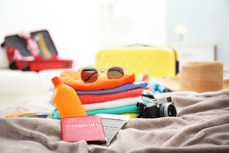 Clothes prepared to packaging in traveler case on bed, closeup