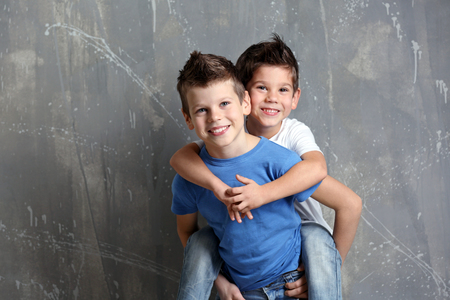 Cute little brothers standing on grey textured background 写真素材