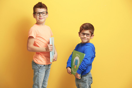 Cute little brothers with books on yellow background