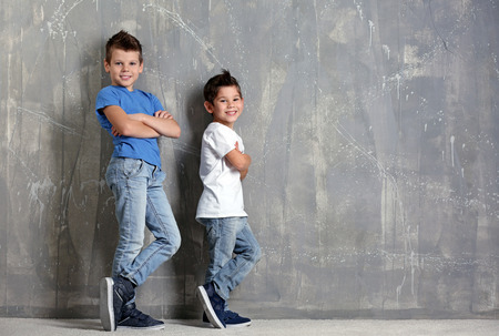 Cute little brothers standing on grey textured background