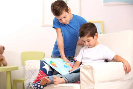 Cute little brothers with books sitting on armchair at home 写真素材