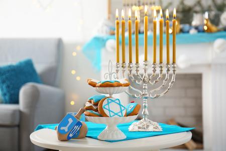 Menorah, dreidels and cookies for Hanukkah on stool in living room, closeup