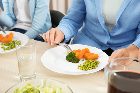 Woman eating vegetables during lunch at home, closeup Stock Photo
