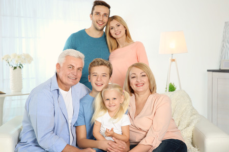 Happy family gathered in living room Imagens