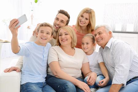 Happy family taking selfie in living room 写真素材