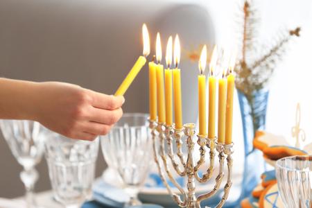 Female hand lighting candles in menorah on table served for Hanukkah Reklamní fotografie