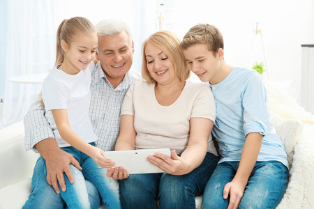Cute children and their grandparents sitting on sofa with tablet computer