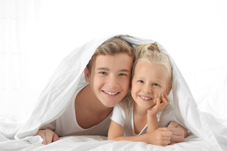 Cute little girl with elder brother lying on bed under white sheet