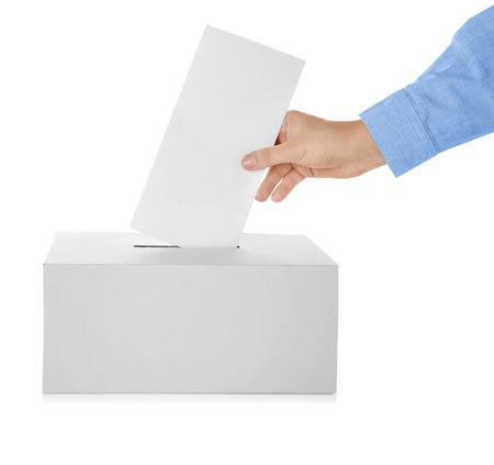 Main masculine mettant le bulletin de vote dans la boîte sur fond blanc
