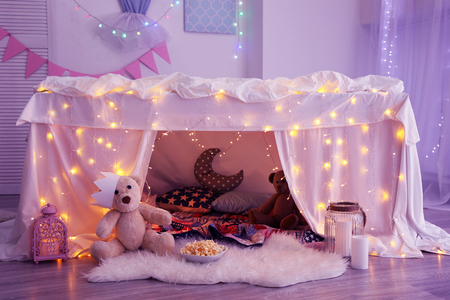 Hovel decorated with garland for childrens party at home Stock Photo
