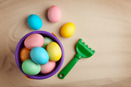 Easter eggs with pail and rake on sand Stock Photo