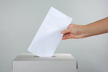 Female hand putting voting ballot into the box  on color background