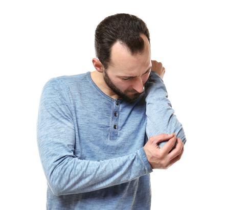 Hübscher Mann, der unter Schmerzen im Ellbogen auf weißem Hintergrund leidet Standard-Bild