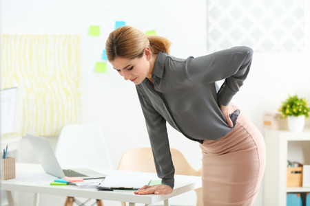 Beautiful woman suffering from backache in office