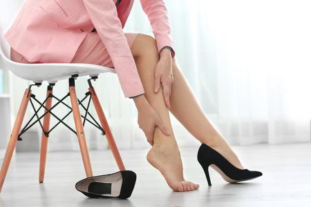 Vrouw die lijdt aan pijn in het been op kantoor