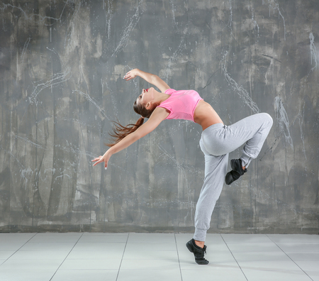 Hip hop dancer dancing on gray background