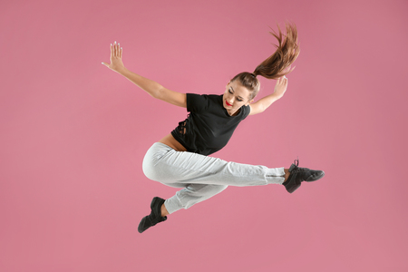 Hip hop dancer dancing on pink background