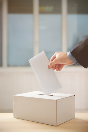 Closeup of hand inserting envelope in ballot box