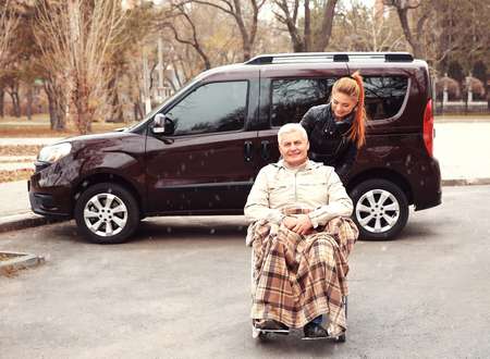 Young woman with man in a wheelchair in front of his car Stock Photo