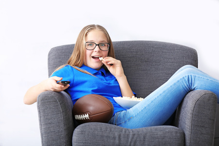 Pretty teenager watching rugby on TV at home Stock Photo - 109928445