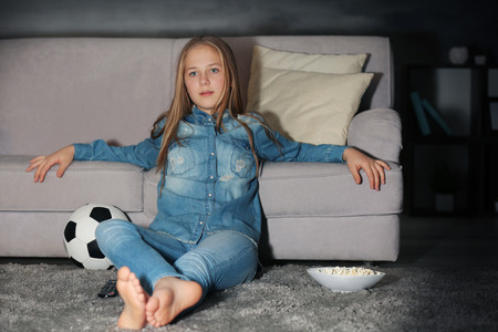 Pretty teenager watching football match late in evening Foto de archivo