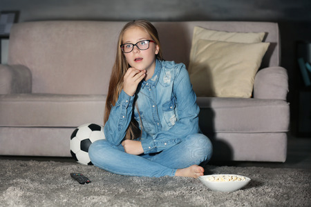 Pretty teenager watching football match late in evening Stockfoto