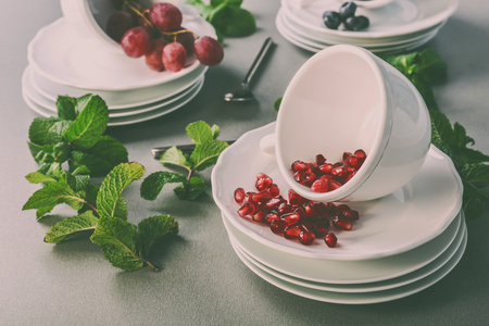 Cups set with grapes, bilberry and garnet on gray background