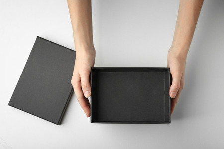 Female hands with black open box on white background